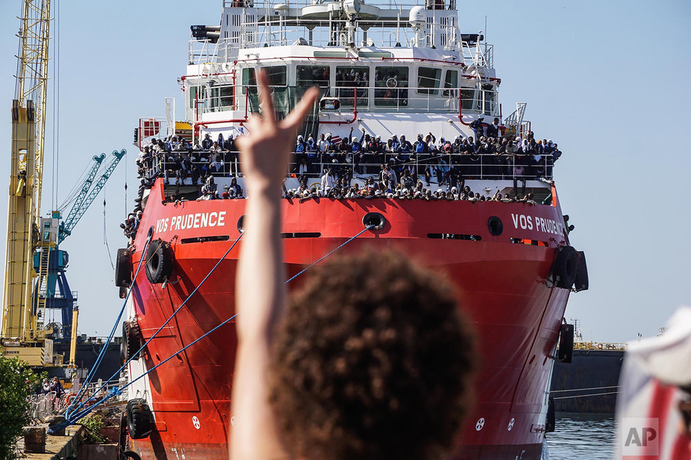 The rescue ship VOS Prudence run by the NGO Medecins Sans Frontieres (MSF) is moored at the Naples harbor, Italy, as migrants wait to be disembarked Sunday, May 28, 2017. On Thursday the VOS Prudence rescued 1,449 people in 12 different operations. MSF also reported a very difficult situation onboard because they had to wait for 2 days as it was not allowed to dock in any Sicilian port due to the G7 summit. (Cesare Abbate/ANSA via AP)