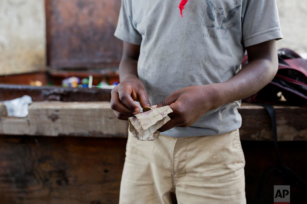 """In this May 23, 2017 photo, 12-year-old Watson Saint Fleur counts his money before going out to buy water bags he sells on the streets of Petion-Ville, a suburb of Port-au-Prince, Haiti. Watson is a """"restavek,"""" a term to describe children whose poor parents hand them over to others. Now he lives at a woman's house but he's fuzzy about how he ended up at her house, only knowing his mother died in his hometown of Petit Goave. He never knew his father. (AP Photo/Dieu Nalio Chery)"""