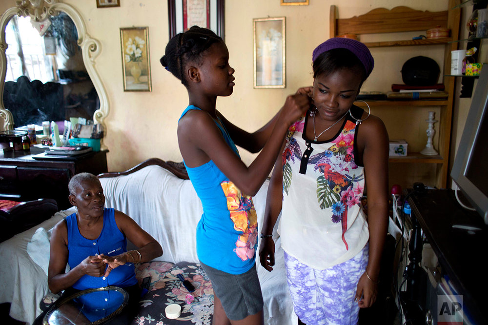 """In this May 27, 2017 photo, 13-year-old Medege Dorlus, center, helps Stephanie, the daughter of Marie Roseline, the lady of the house, with an earring, as Marie Roseline looks on at their home in Port-au-Prince, Haiti. Medege lives with five members of the family that took her in when her mother died, but """"Living with your mom isn't the same as living with your extended family"""" she said. (AP Photo/Dieu Nalio Chery)"""