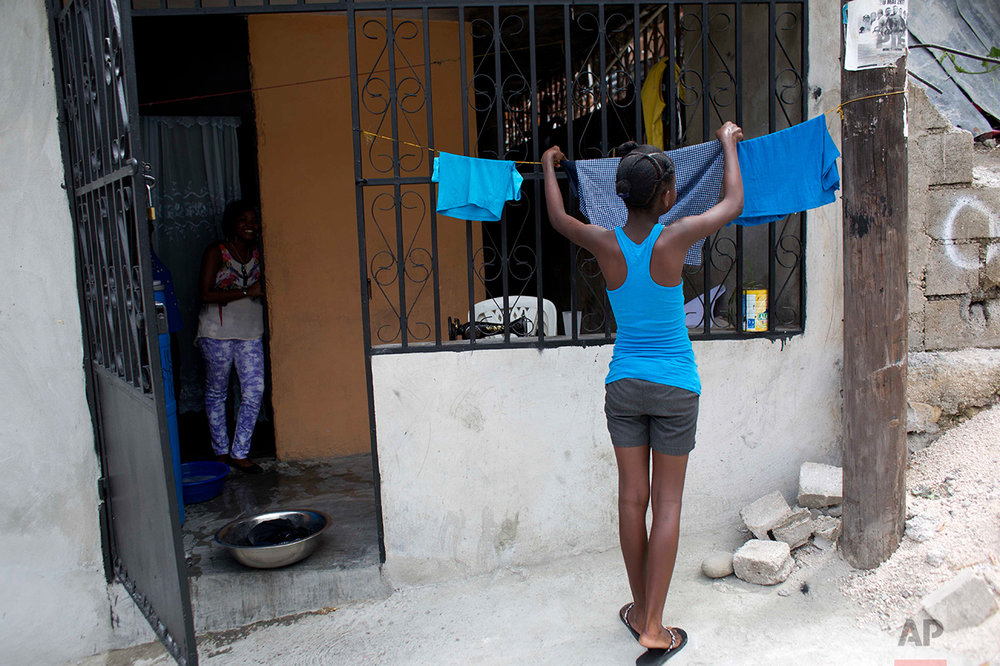 In this May 27, 2017 photo, 13-year-old Medege Dorlus hangs laundry to dry at the home of the family who took her in, in Port-au-Prince, Haiti. Medege is able to go to a state school in the morning but in the afternoon she comes home to domestic chores. (AP Photo/Dieu Nalio Chery)