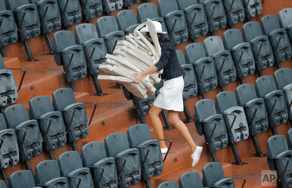 In this Tuesday, June 6, 2017 photo, a hostess removes seat cushion as rain delays the play between France's Kristina Mladenovic and Timea Bacsinszky of Switzerland during their quarterfinal match of the French Open tennis tournament at the Roland Garros stadium in Paris. (AP Photo/Michel Euler)