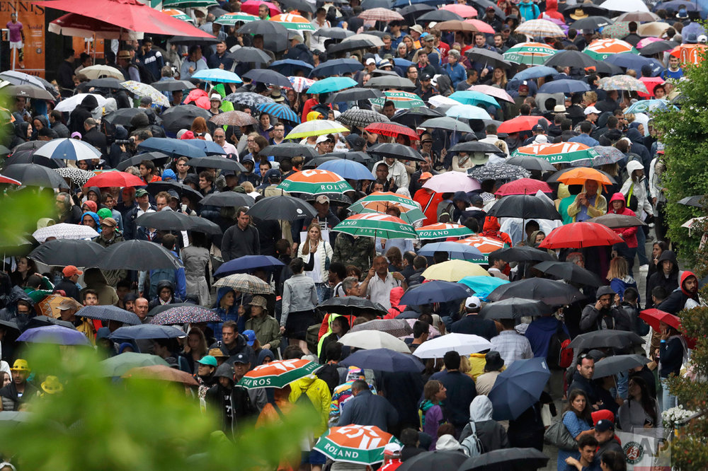 In this Saturday, June 3, 2017 photo, spectators take cover under umbrellas as third round matches were suspended because of rain showers at the French Open tennis tournament at the Roland Garros stadium, in Paris, France. (AP Photo/Petr David Josek)