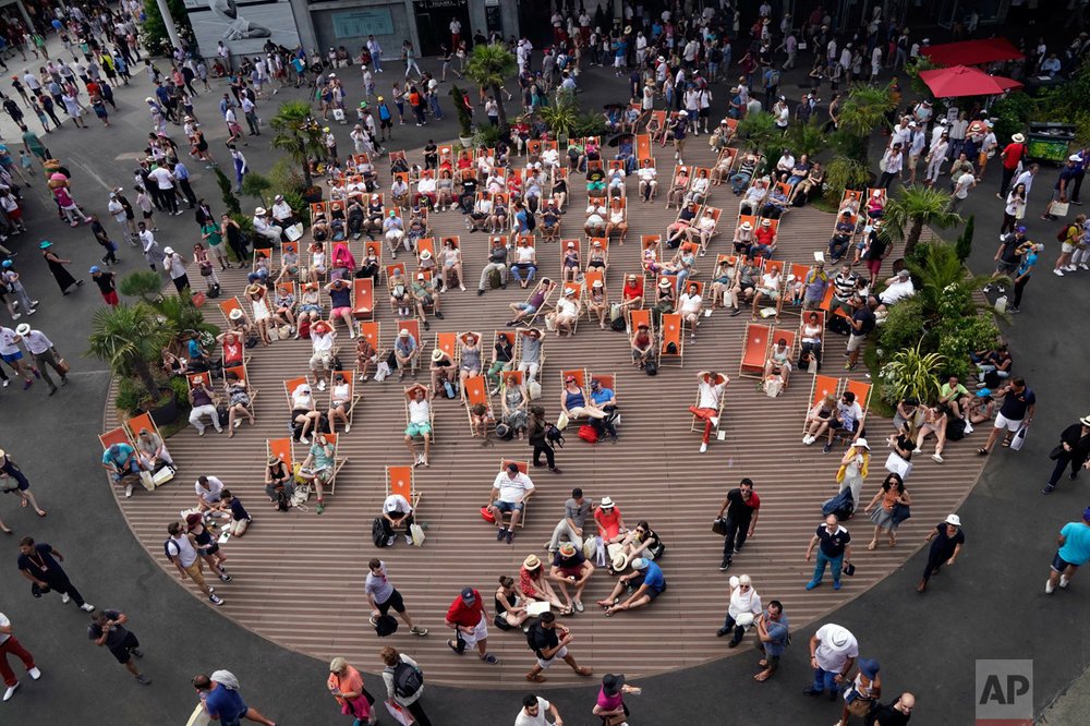 In this Sunday, May 28, 2017 photo, spectators sitting in folding chairs watch a match during the French Open tennis tournament at the Roland Garros stadium in Paris. (AP Photo/Christophe Ena)
