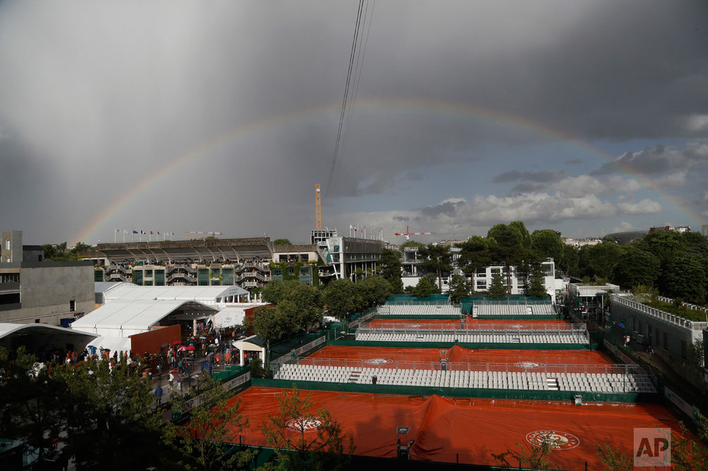In this Tuesday, June 6, 2017 photo, a rainbow sits in the sky over covered courts as rain showers suspended the quarterfinal match of Denmark's Caroline Wozniacki and Latvia's Jelena Ostapenko of the French Open tennis tournament at the Roland Garros stadium, in Paris, France. (AP Photo/Petr David Josek)