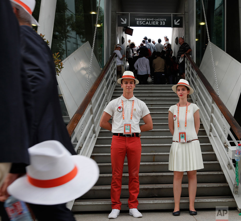 A hostess and host wait to welcome spectators at the Roland Garros stadium where the French Open tennis tournament is taking place in Paris, France. Friday, June 2, 2017. (AP Photo/Christophe Ena)