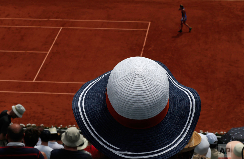 In this Sunday, May 28, 2017 photo, a spectator watches Petra Kvitova of the Czech Republic play Julia Boserup, of the U.S, during their first round match of the French Open tennis tournament at the Roland Garros stadium in Paris. (AP Photo/Petr David Josek)