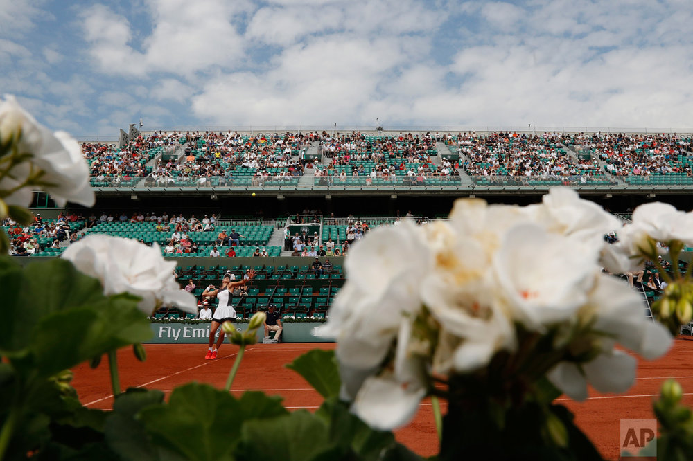 In this Friday, June 2, 2017 photo, Spain's Garbine Muguruza serves the ball to Kazakhstan's Yulia Putintseva during their third round match of the French Open tennis tournament at the Roland Garros stadium in Paris. (AP Photo/Petr David Josek)