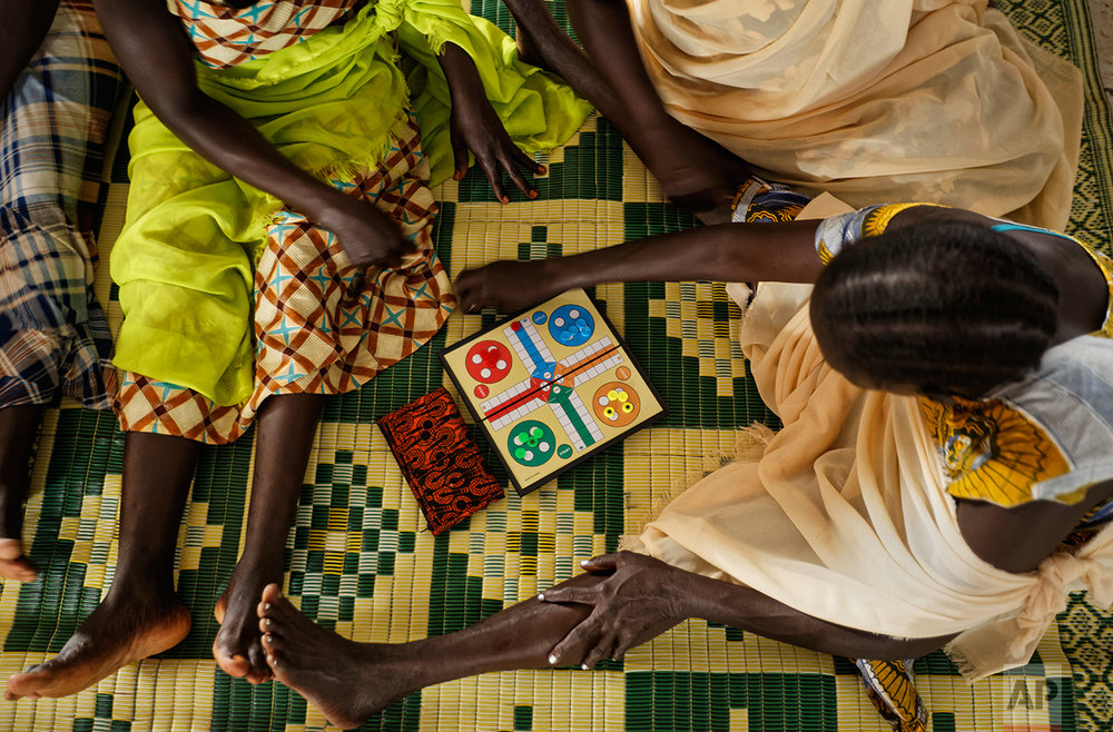 In this photo taken Saturday, June 3, 2017, South Sudanese refugee women who suffered sexual or other gender-based violence play a board game at a women's center focusing on such violence, run by the aid group International Rescue Committee, in Bidi Bidi, Uganda. (AP Photo/Ben Curtis)