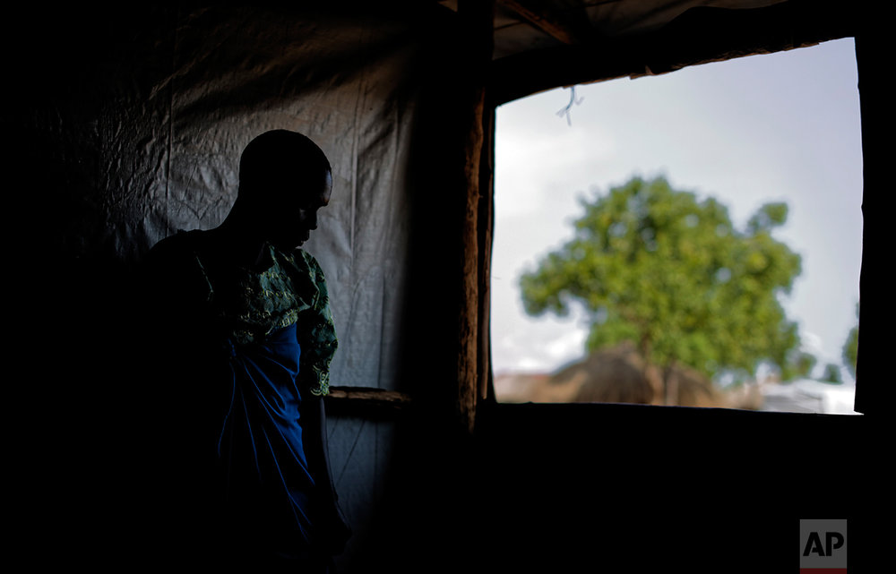 In this photo taken Saturday, June 3, 2017, a South Sudanese refugee and 32-year-old mother, who was raped for several days by a group of soldiers before she was allowed to leave, stands by a window at a women's center focusing on gender-based violence, run by the aid group International Rescue Committee, in Bidi Bidi, Uganda. (AP Photo/Ben Curtis)