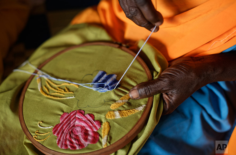 In this photo taken Saturday, June 3, 2017, a South Sudanese refugee woman who suffered sexual or gender-based violence embroiders a bed sheet at a women's center focusing on such violence, run by the aid group International Rescue Committee, in Bidi Bidi, Uganda. (AP Photo/Ben Curtis)