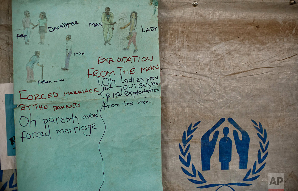 In this photo taken Saturday, June 3, 2017, a sign promoting knowledge of gender issues hangs on the wall at a women's center for South Sudanese refugees focusing on sexual and gender-based violence, run by the aid group International Rescue Committee, in Bidi Bidi, Uganda. (AP Photo/Ben Curtis)
