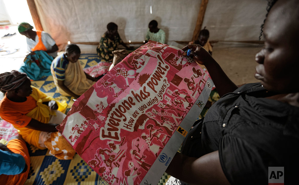 In this photo taken Saturday, June 3, 2017, Lilian Dawa, right, a South Sudanese refugee from Yei who manages a women's center focusing on gender-based violence, shows some of the informational material used at the center, run by the aid group International Rescue Committee, in Bidi Bidi, Uganda.  (AP Photo/Ben Curtis)