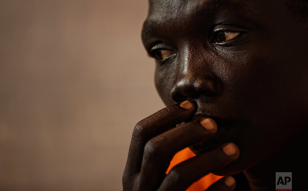 In this photo taken Saturday, June 3, 2017, a South Sudanese refugee recounts her experience, at a women's center focusing on sexual and gender-based violence, run by the aid group International Rescue Committee, in Bidi Bidi, Uganda. (AP Photo/Ben Curtis)