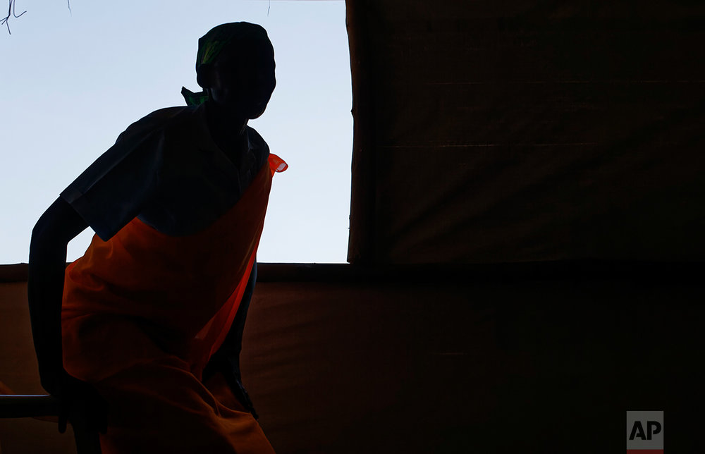 In this photo taken Saturday, June 3, 2017, South Sudanese refugee Joy Diko, who escaped unhurt when government soldiers besieged her town Yei and dragged her teenage daughter outside taking turns raping her as she cried for help, sits by a window in a women's center focusing on gender-based violence, run by the aid group International Rescue Committee, in Bidi Bidi, Uganda. (AP Photo/Ben Curtis)