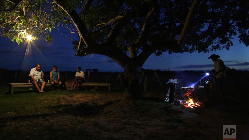 "In this May 17, 2017 photo, cowboys chat as they eat a ""churrasco,"" or barbecue, at a ranch in Corumba, in the Pantanal wetlands of Mato Grosso do Sul state, Brazil. Each day, the men and animals traverse about 11 miles from dawn until 3 p.m., in temperatures averaging about 90 degrees Fahrenheit during the day.  (AP Photo/Eraldo Peres)"