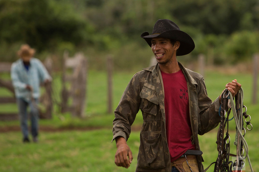 In this May 16, 2017 photo, cowboy Renan Lopes Nascimento holds his reigns as he arrives to a ranch to spend the night, in Corumba, in the Pantanal wetlands of Mato Grosso do Sul state, Brazil. Cowboys earn an average of $18 dollars a day, and the leader of the group can earn as much as $285 per day. (AP Photo/Eraldo Peres)