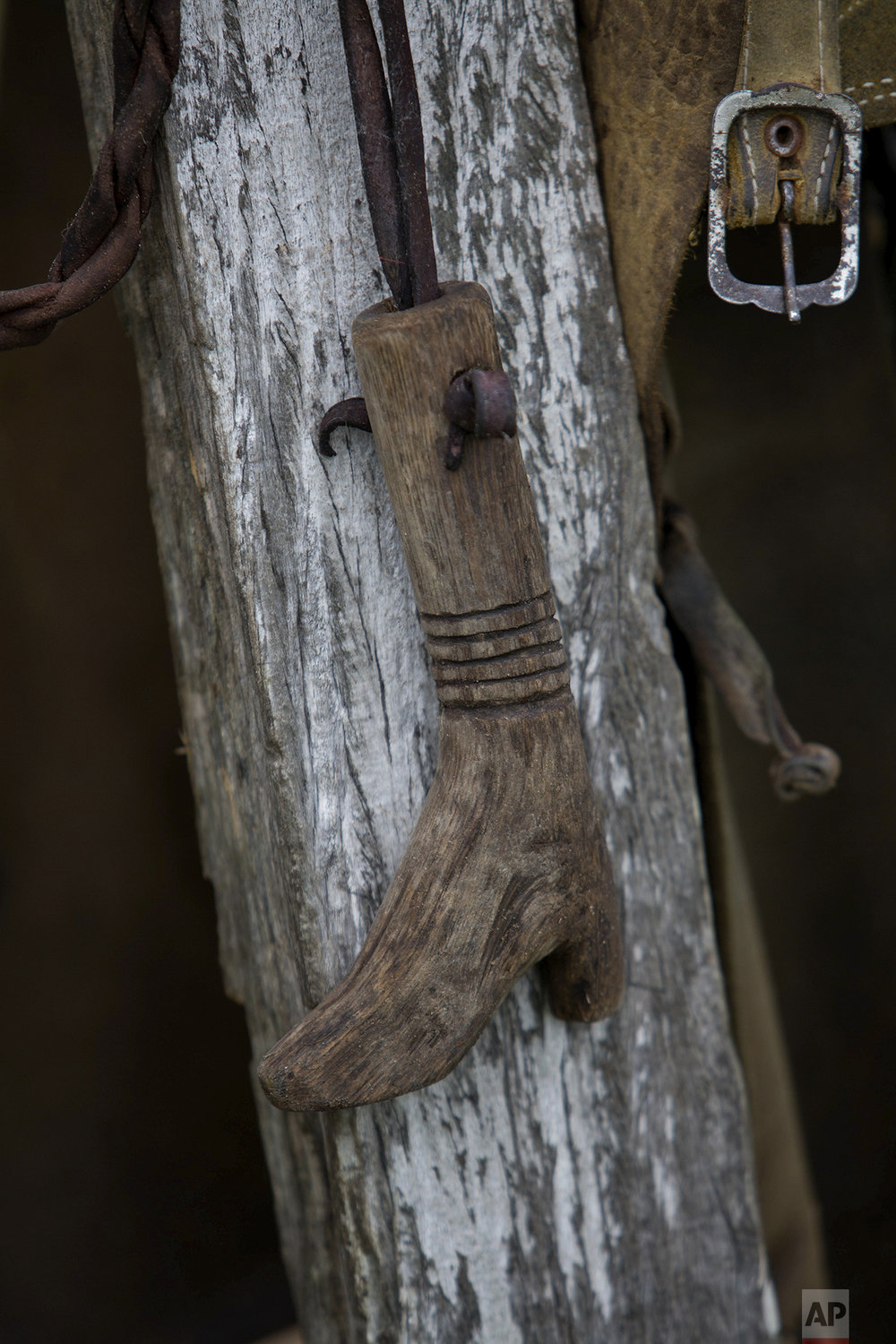 In this May 16, 2017 photo, a handmade whip handle, in the shape of a boot, hangs in a cowboy camp in Corumba, in the Pantanal wetlands of Mato Grosso do Sul state, Brazil. The whip was made by one of the ranch hands who helps round up cattle. (AP Photo/Eraldo Peres)