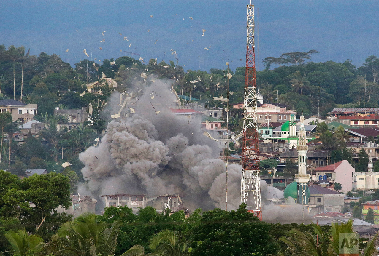 "Debris flies in the air as Philippine Air Force fighter jets bomb suspected locations of Muslim militants as fighting continues in Marawi city, southern Philippines Friday, June 9, 2017. It's unclear how many people remain trapped in Marawi as government troops battle Muslim militants led by the ""Maute"" group, but army officers have put the figure this week at anywhere from 150 to 1,000. (AP Photo/Aaron Favila)"