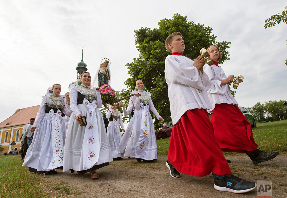 Women dressed in the traditional clothes of the Sorbs carry the statue of Virgin Mary during a procession in front of the church in Rosenthal, eastern Germany, Monday, June 5, 2017. On White Monday, Catholic Sorbs, a Slavic minority near the German-Polish border, celebrate an open air mass in the small village east of Dresden. (AP Photo/Jens Meyer)