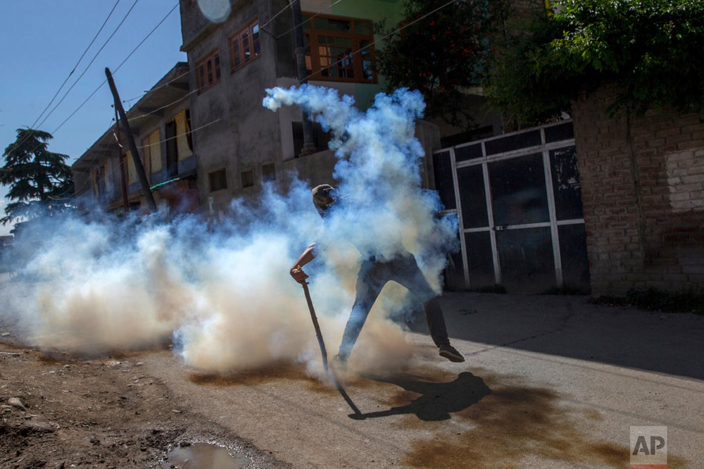 A Kashmiri protester throws back a detonated tear gas shell at Indian police during a protest in Srinagar, Indian controlled Kashmir, on Friday, June 9, 2017. Parts of Indian-controlled Kashmir remained under curfew Friday, while general strikes were being staged in other areas after Kashmiri separatists called for strike to protest the Tuesday killing of a civilian by government forces during a search operation to flush out Kashmiri rebels in the southern town of Indian controlled Kashmir. (AP Photo/Dar Yasin)