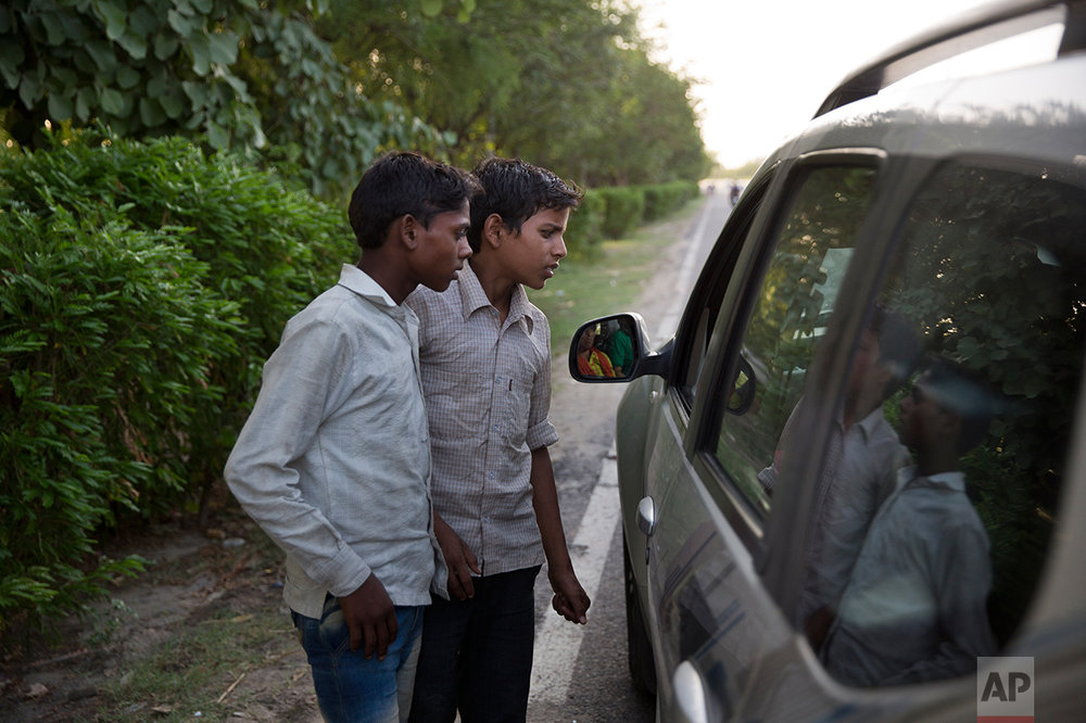 In this Thursday June 8, 2017 photo, Indian boys Salish 15, left, and Sachin 12, listen to their customer as they sell cooked corn along a busy expressway in Noida, India. Every 100 meters (330 feet) or so there are children selling corn along this busy expressway on the outskirts of New Delhi. According to India's 2011 census, boys them him are part of the estimated 8.3 million child laborers In India. Uttar Pradesh state, where Noida is located, alone accounts for 1.8 million of that total. (AP Photo/Tsering Topgyal)