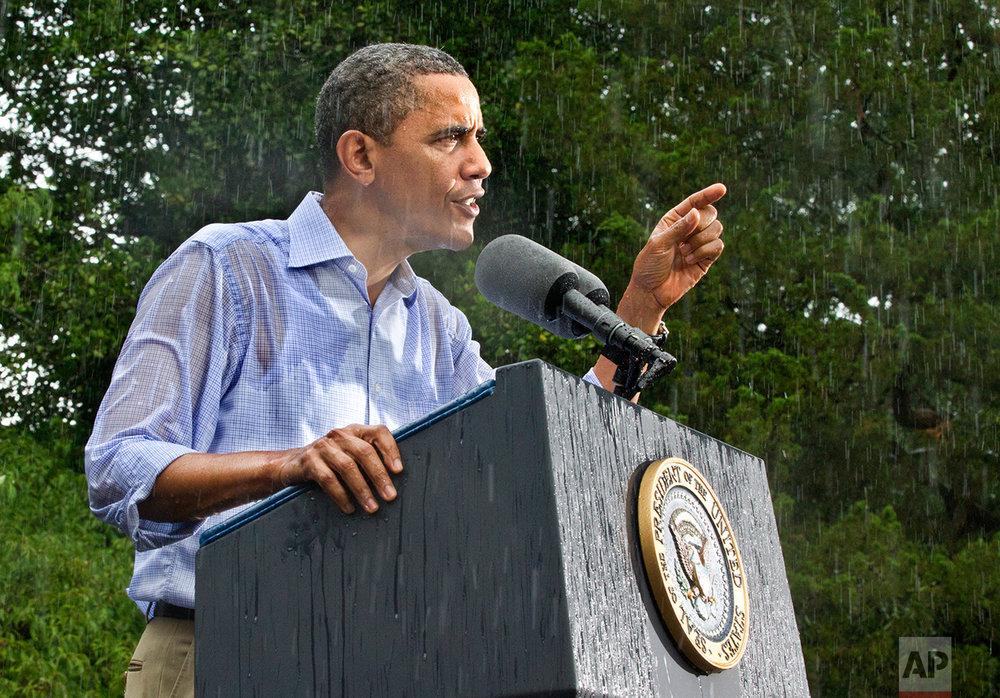 President Barack Obama campaigns for re-election in the heavy rain at Walkerton Tavern & Gardens in Glen Allen, Va., near Richmond, Saturday, July 14, 2012. (AP Photo/J. Scott Applewhite)