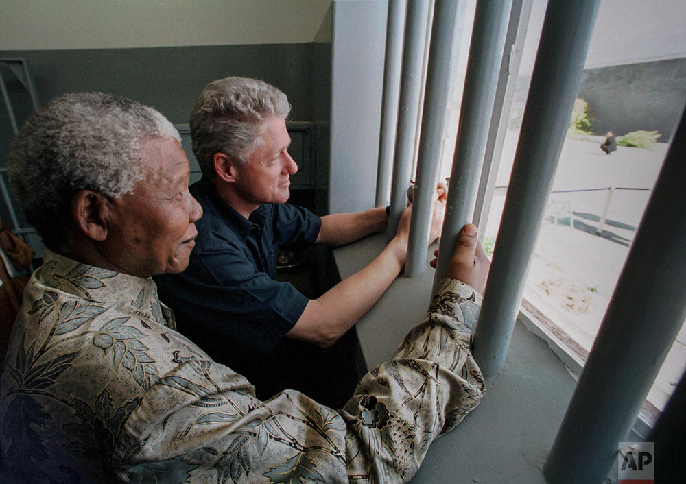 In this March 27, 1998 photo, South African President Nelson Mandela, foreground, and U.S. President Bill Clinton peer out from Section B, prison cell No. 5, on Robben Island, South Africa.  (AP Photo/J. Scott Applewhite)