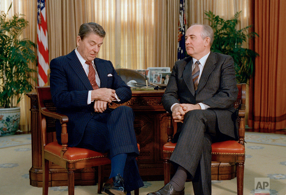 President Ronald Reagan checks his watch while talking with Soviet leader Mikhail Gorbachev during a meeting in the White House Oval Office, Dec. 9, 1987.  Reagan and Gorbachev were meeting for the third time in two days.  (AP Photo/J. Scott Applewhite)
