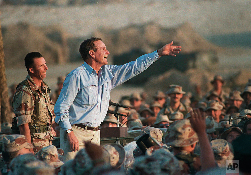 President George Bush tosses presidential tie clips to U.S. Marines at a desert encampment in eastern Saudi Arabia, Nov. 23, 1990 during a Thanksgiving Day visit. (AP Photo/J. Scott Applewhite)