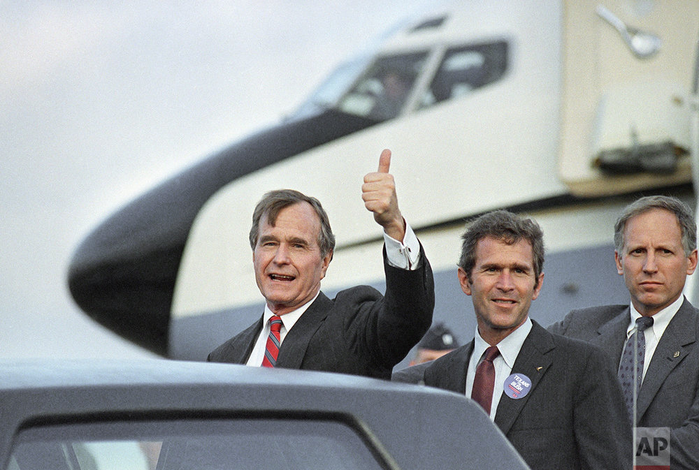 U.S. Vice-President George Bush gives the thumbs up sign after being greeted by his son George Jr., right, upon arriving in Houston, Monday, Nov. 7, 1988. (AP Photo/J. Scott Applewhite)
