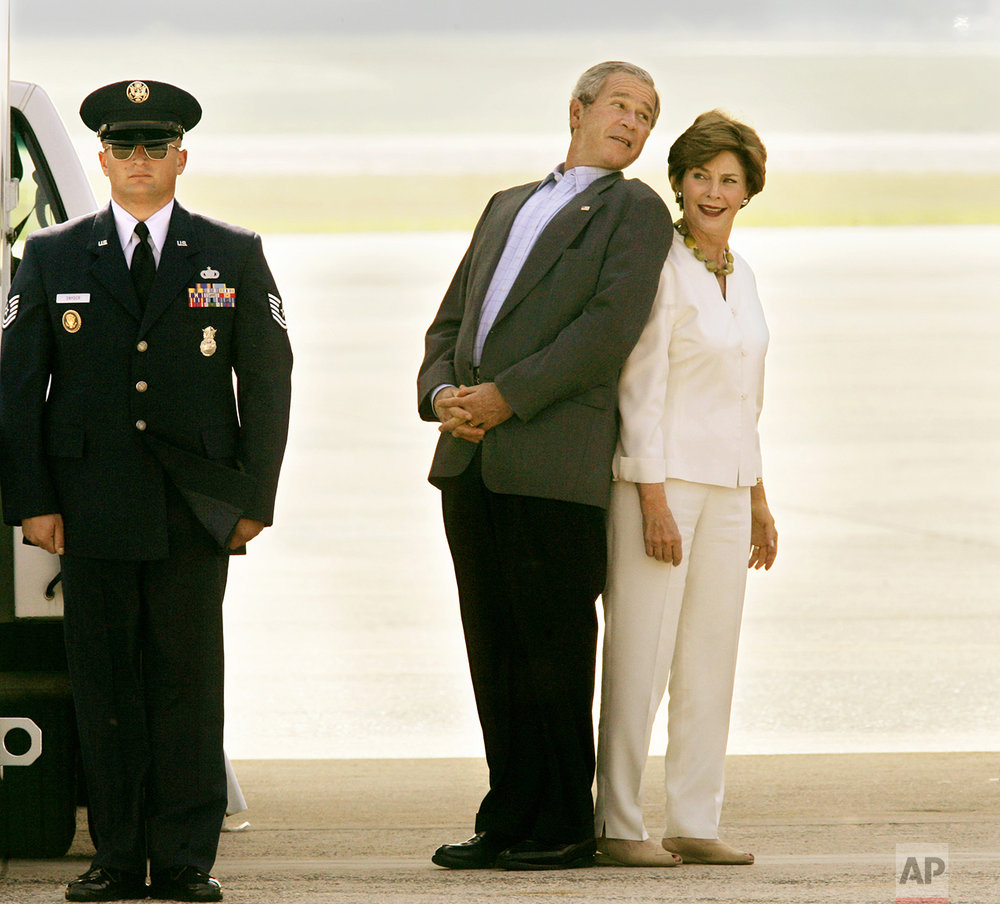 President Bush teases with first lady Laura Bush under the belly of Air Force One as they wait for Japan's Prime Minister Junichiro Koizumi to arrive for a trip to Memphis, Tenn., Friday, June 30, 2006, at Andrews Air Force Base, Md. (AP Photo/J. Scott Applewhite)