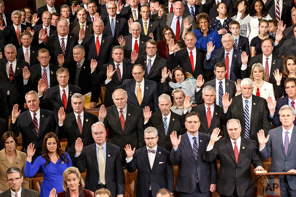 Members of the House of Representatives on the GOP side raise their hands for the oath of office at the opening session of the 114th Congress, at the Capitol in Washington, Tuesday, Jan. 6, 2015. House Speaker John Boehner, R-Ohio, won a third term despite a tea party-backed effort to unseat him. (AP Photo/J. Scott Applewhite)