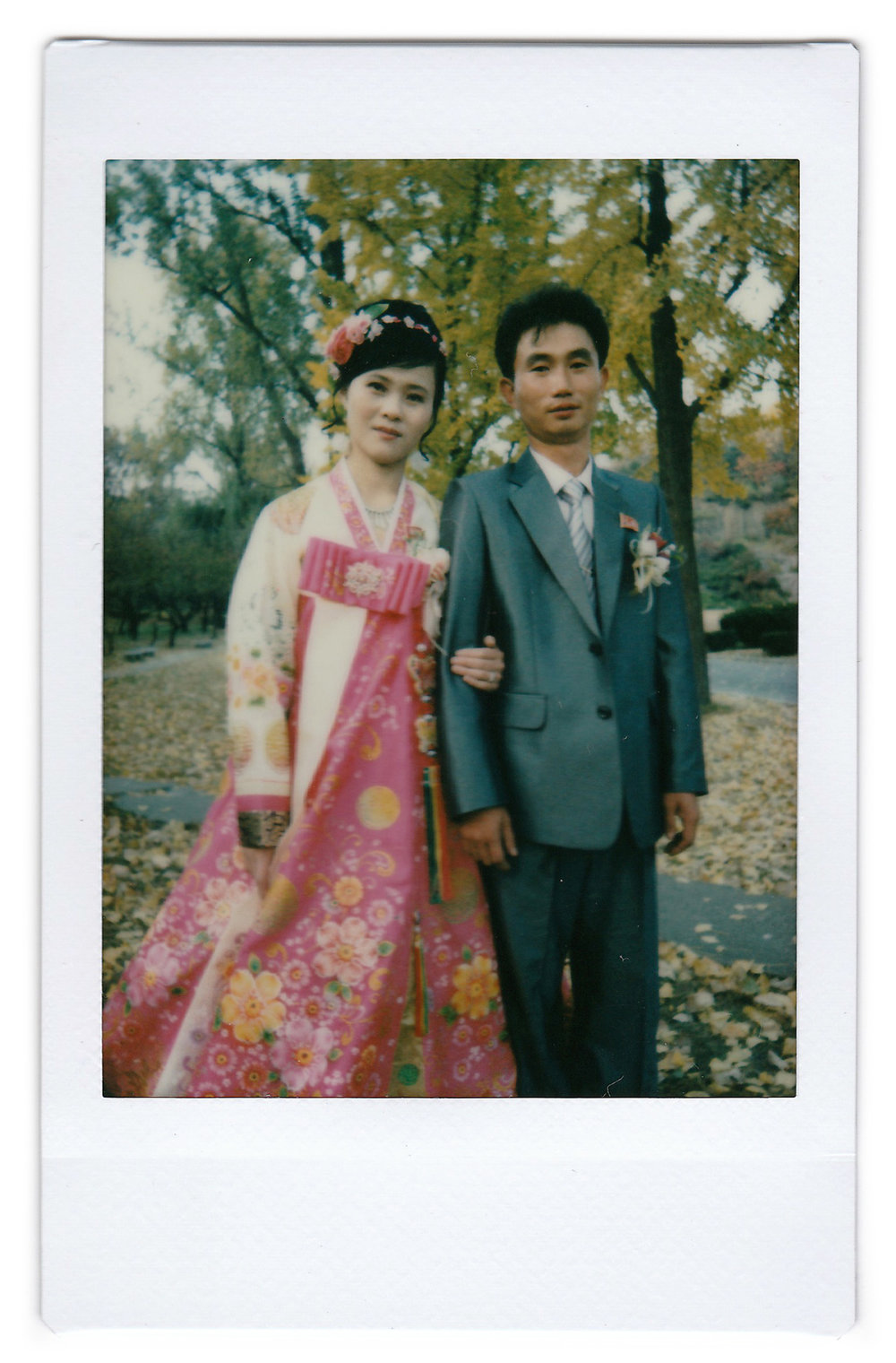 In this Oct. 25, 2014, photo made with an instant camera, North Korean bride Ri Ok Ran, 28, and groom Kang Sung Jin, 32, pose for a portrait at the Moran Hill where they went to take wedding pictures, in Pyongyang, North Korea. The couple were married after dating for about two years. (AP Photo/Wong Maye-E)