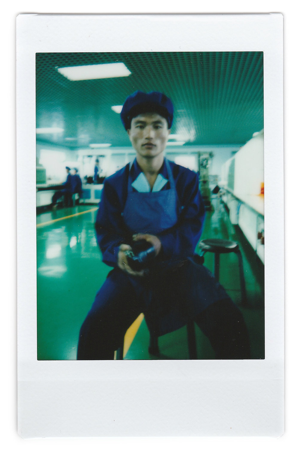 "In this June 22, 2016, photo made with an instant camera, Kang Jong Jin, a 28-year old former soldier who attaches soles onto shoes at a shoe factory in Wonsan, North Korea, poses for a portrait at his work station. Kang, who has been working longer hours during this 200-day ""speed campaign"" in line with North Korean leader Kim Jong Un's vows to raise the nation's standard of living and energize his five-year plan to develop economy, says that he wants to contribute to Kim's plan by taking courses to improve his scientific and technological skills. (AP Photo/Wong Maye-E)"