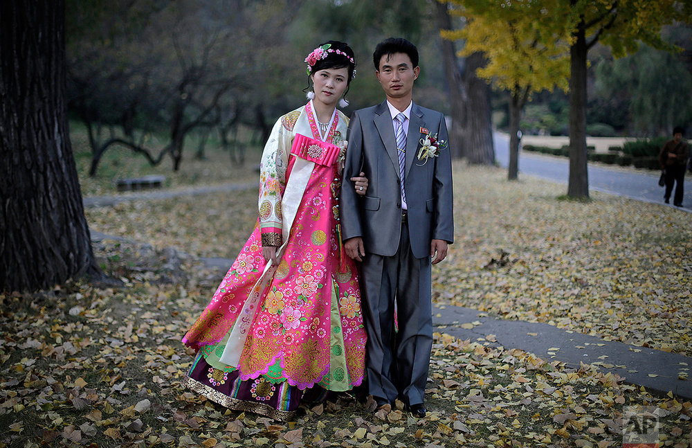 "In this Oct. 25, 2014, file photo, North Korean bride Ri Ok Ran, 28, and groom Kang Sung Jin, 32, pose for a portrait at the Moran Hill where they went to take wedding pictures, in Pyongyang, North Korea. The couple were married after dating for about two years. Their motto: ""To have many children so that they can serve in the army and defend and uphold our leader and country, for many years into the future.""  (AP Photo/Wong Maye-E)"