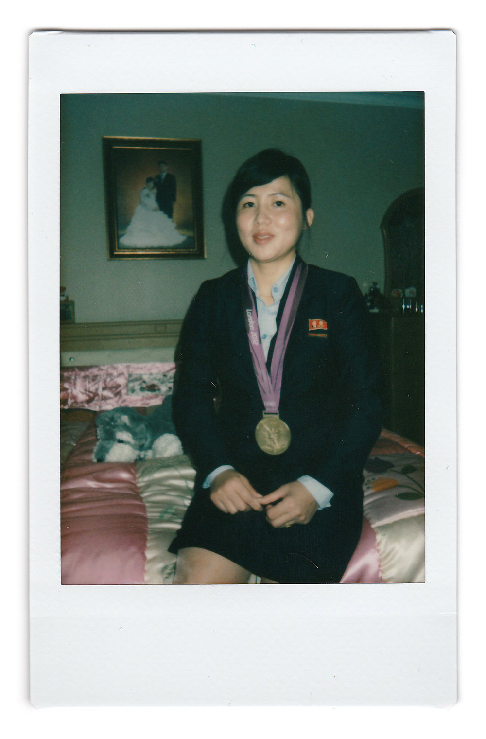 In this Oct. 23, 2014, photo made with an instant camera, North Korean London 2012 Olympics Judo gold medalist, An Kum Ae poses in her bedroom with her gold medal in Pyongyang, North Korea. When asked what's important to them, North Koreans might talk about working hard, or doing well at sports, or having a big family, but leader Kim Jong Un is never far from the conversation.(AP Photo/Wong Maye-E)