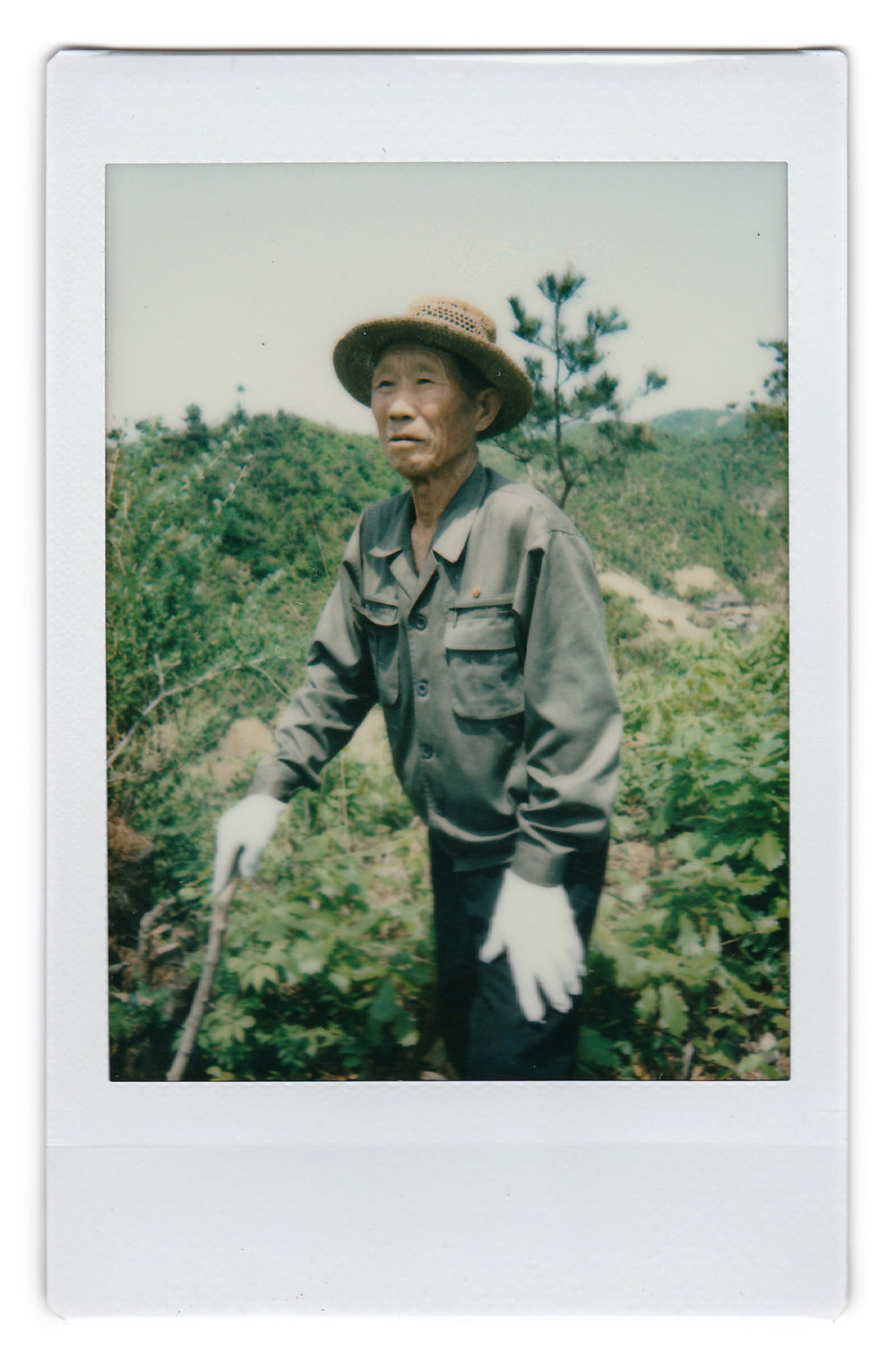 In this May 8, 2017, photo made with an instant camera, village elder Kim Ri Jun, 77, poses for a portrait on Ryongyon-ri hill in Kujang county, North Korea. Kim was 13-years old when the Korean War broke out. Kim and his friend have been helping to move and bury soldier remains believed to be that of American soldiers up this hill, as the area where the remains were once buried is now constructed into a power dam. When asked what's important to them, North Koreans might talk about working hard, or doing well at sports, or having a big family, but leader Kim Jong Un is never far from the conversation. (AP Photo/Wong Maye-E)