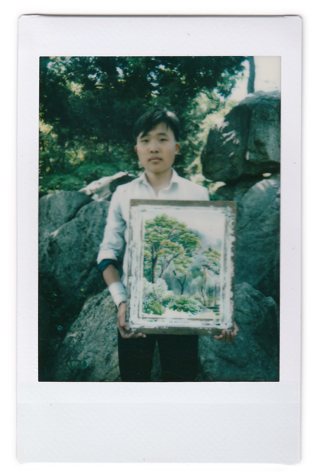 "In this May 10, 2015, photo made with an instant camera, Pak Sin Hyok, 16, a student of the Pyongyang University of Fine Art, poses with his unfinished water-color painting of trees in Moranbong or Moran Hill, in Pyongyang, North Korea. Pak has been studying art for three years and hopes to be a professional artist after he graduates in this course that lasts for nine years. When asked what's important to them, North Koreans might talk about working hard, or doing well at sports, or having a big family, but leader Kim Jong Un is never far from the conversation. His motto: ""To give focus to producing Juche-oriented art and bring glory to the Juche idea, which is the idea of self-reliance."" (AP Photo/Wong Maye-E)"
