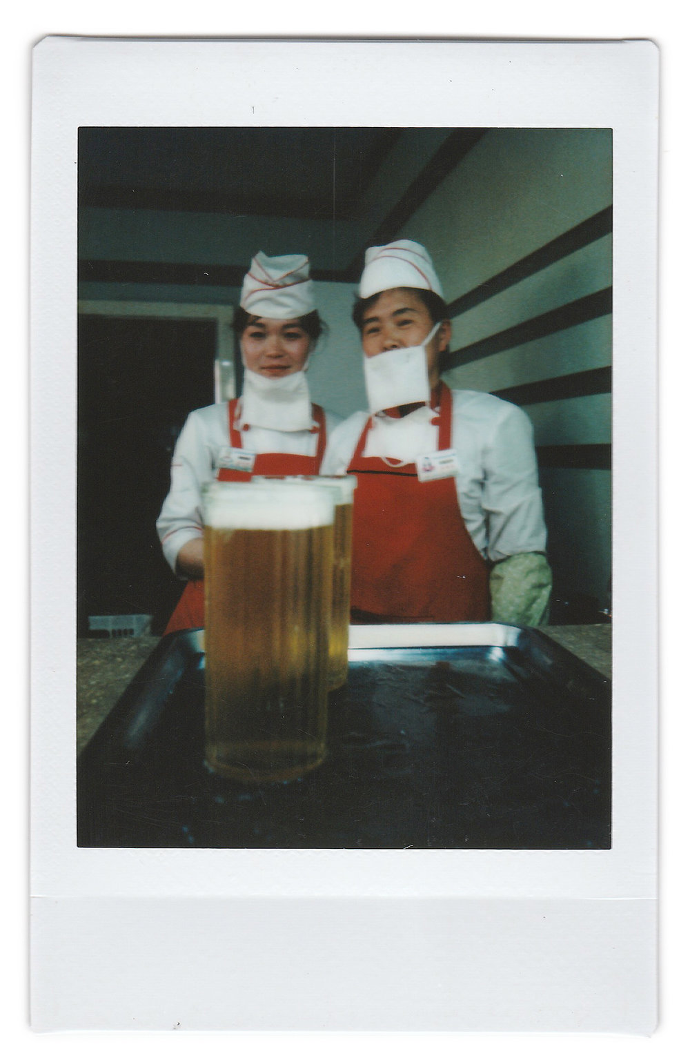"In this May 7, 2016, photo made with an instant camera, beer servers Kim Yon Hui, 29, left, and Yang Pok Yong, 42, right, pose for a portrait while they wait to serve customers at the Taedonggang Beer shop, in Pyongyang, North Korea. Kim has been working as a server for over a year and likes her job because she likes ""seeing many people enjoy themselves under the deep care of the dear leader."" Kim's motto: ""To serve the people."" Yang is also ""pleased when people enjoy themselves at the beer shop"". Yang's motto: ""To please our leader by working hard for the people in my country.""  When asked what's important to them, North Koreans might talk about working hard, or doing well at sports, or having a big family, but leader Kim Jong Un is never far from the conversation. (AP Photo/Wong Maye-E)"