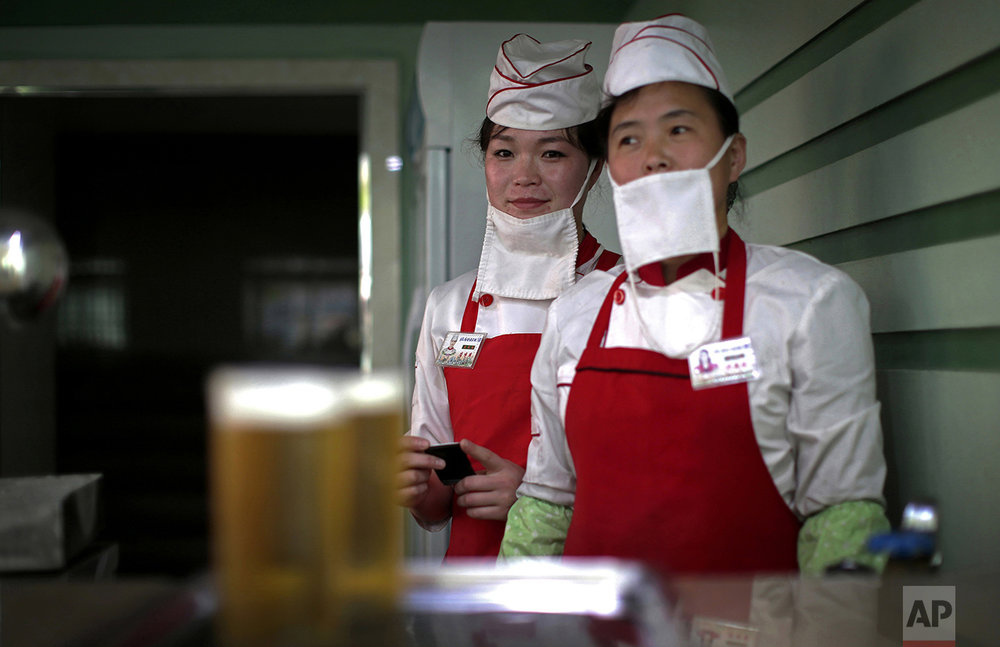 "In this May 7, 2016, photo, beer servers Kim Yon Hui, 29, left, and Yang Pok Yong, 42, right, pose for a portrait while they wait to serve customers at the Taedonggang Beer shop, in Pyongyang, North Korea. Kim has been working as a server for over a year and likes her job because she likes ""seeing many people enjoy themselves under the deep care of the dear leader."" Kim's motto: ""To serve the people."" Yang is also ""pleased when people enjoy themselves at the beer shop"". Yang's motto: ""To please our leader by working hard for the people in my country.""  (AP Photo/Wong Maye-E)"