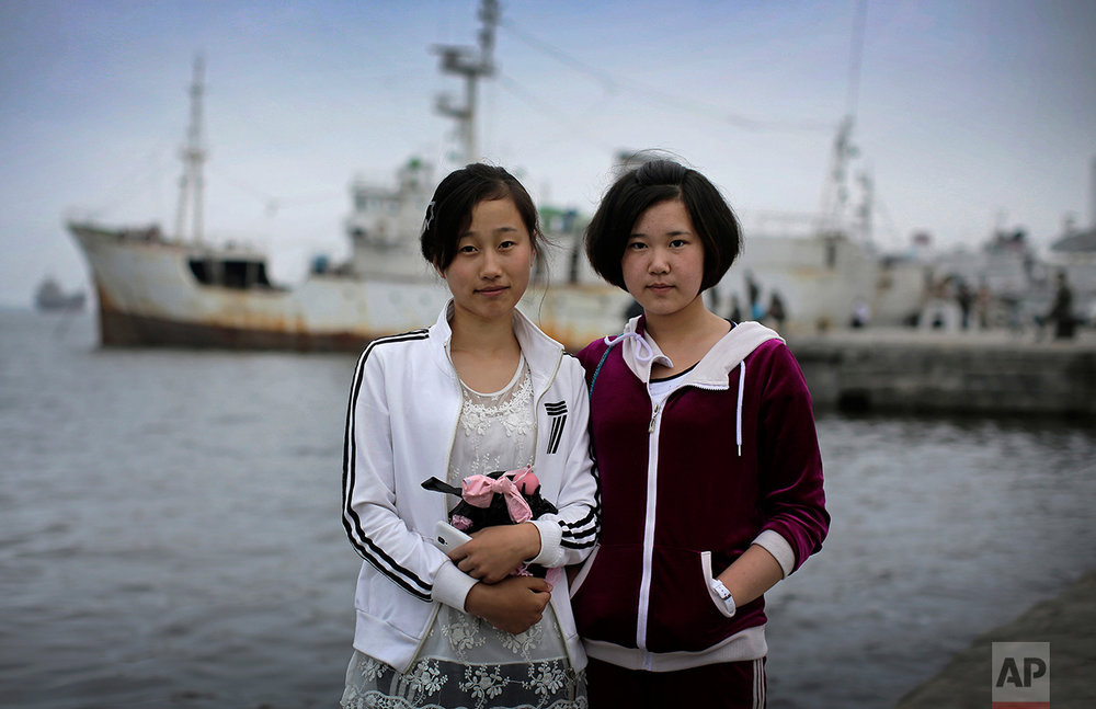 "In this June 21, 2016, photo, Ri Nam Hae, left, and Kil Myong Kyong, both 16-years old, pose for a portrait at a pier in Wonsan, North Korea. Ri wants to be a journalist and her motto is to ""spread the country's propaganda to the world. "" Kil's motto: ""I want to uphold Marshal Kim Jong Un and North Korea with my rifle."" (AP Photo/Wong Maye-E)"