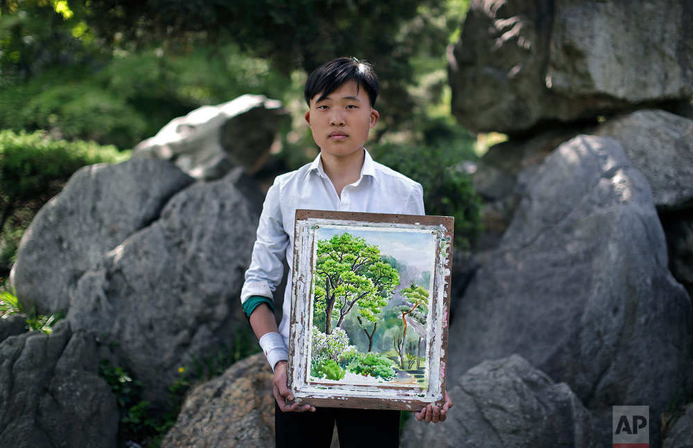 "In this May 10, 2015, photo, Pak Sin Hyok, 16, a student of the Pyongyang University of Fine Art, poses with his unfinished water-color painting of trees in Moranbong or Moran Hill, in Pyongyang, North Korea. Pak has been studying art for three years and hopes to be a professional artist after he graduates in this course that lasts for nine years. His motto: ""To give focus to producing Juche-oriented art and bring glory to the Juche idea, which is the idea of self-reliance."" (AP Photo/Wong Maye-E)"