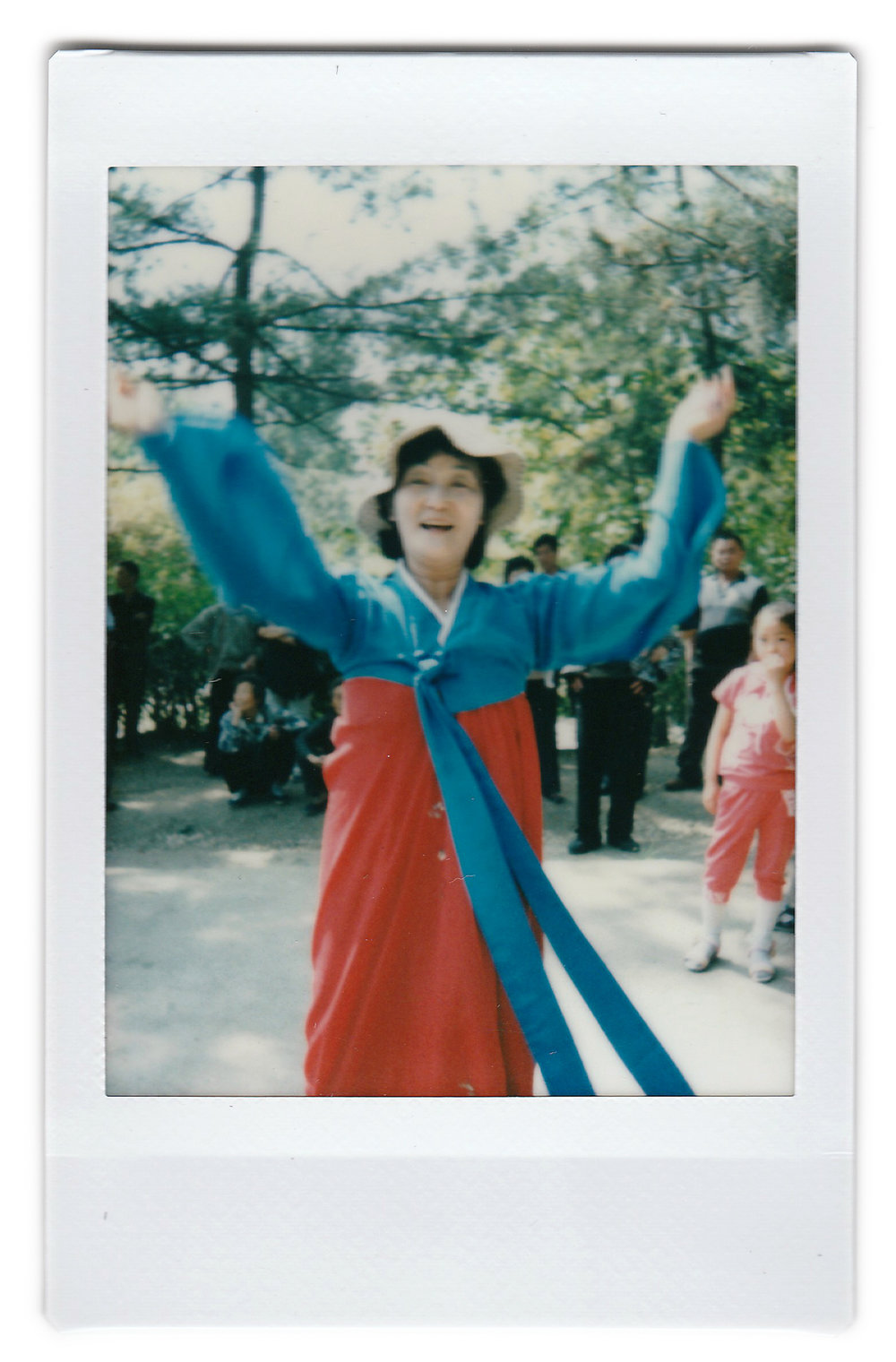 "In this May 10, 2015, photo made with an instant camera, Ri Chun Im, 71, poses for a portrait as she dances with other elderly North Korean men and women at a park in Moran Hill in Pyongyang, North Korea. Ri has been dancing everyday for the past 4-5 years. She loves dancing because it keeps her young and healthy. When asked what's important to them, North Koreans might talk about working hard, or doing well at sports, or having a big family, but leader Kim Jong Un is never far from the conversation. Her motto: ""To live a healthy life devoted to supporting the country's ruling party."" (AP Photo/Wong Maye-E)"