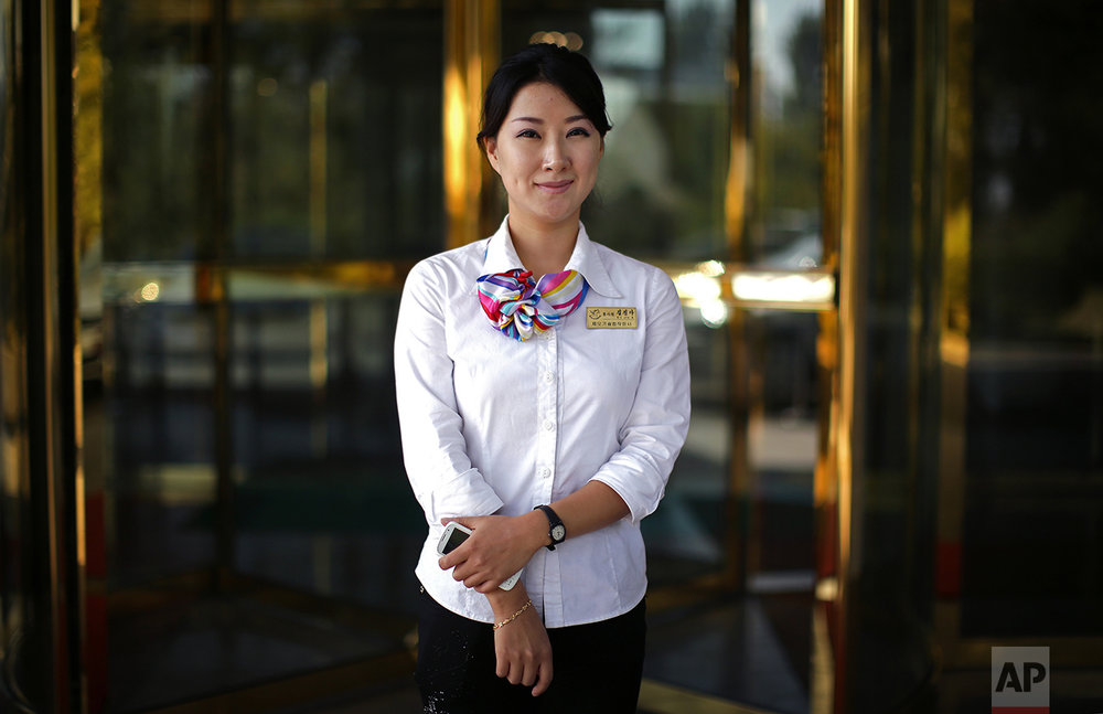 "In this Oct. 14, 2015, photo, Kil Jin A, 29, poses for a portrait at the entrance of the Pothonggang Hotel where she works with mobile phone service provider Koryolink, in Pyongyang, North Korea. She has been working with Koryolink for 8 years and enjoys her job as a sales executive because it gives her opportunities to meet visitors from abroad.  Her motto: ""To always help others, but of course, patriotism towards my country is most important."" (AP Photo/Wong Maye-E)"