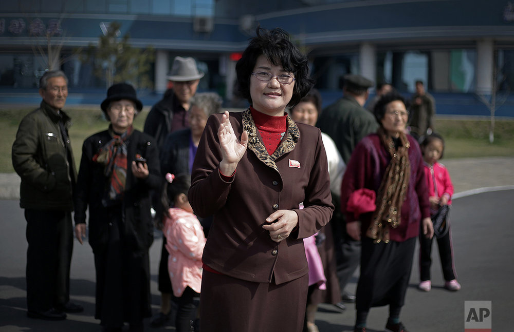"In this April 9, 2017, photo, Sin Ye Suk, 50, a homemaker and the chief of the people's unit at the apartment block she lives in at Mirae Scientists Street, poses for a portrait with fellow residents in the background on Sunday, April 9, 2017, in Pyongyang, North Korea. Her motto: ""I devote my life to helping others."" (AP Photo/Wong Maye-E)"