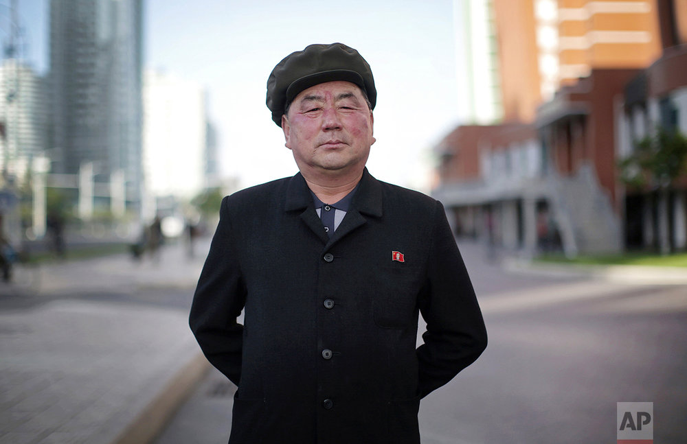 "In this May 7, 2016, photo, Pak Su Won, 66, a retired local physician, poses for a portrait along Mirae Scientists Street in Pyongyang, North Korea. His motto: ""To devote myself to leader Kim Jong Un for the rest of my life. For him, and for the fatherland."" (AP Photo/Wong Maye-E)"