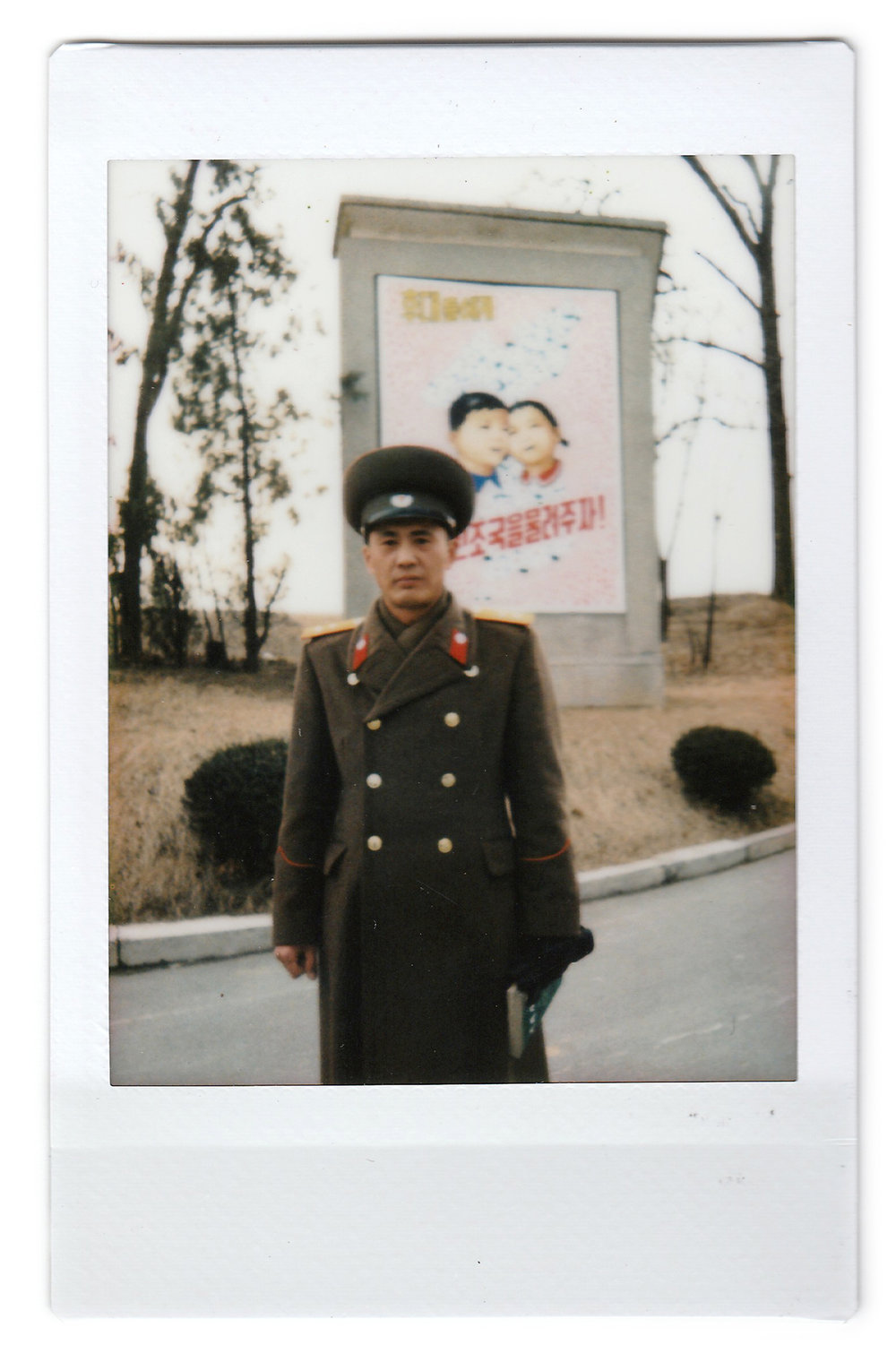 In this Feb. 22, 2016, photo made with an instant camera, North Korean People's Army Lt. Col. Nam Dong Ho poses for a portrait at the entrance to the Demilitarized Zone (DMZ) on the North Korean side. When asked what's important to them, North Koreans might talk about working hard, or doing well at sports, or having a big family, but leader Kim Jong Un is never far from the conversation. (AP Photo/Wong Maye-E)