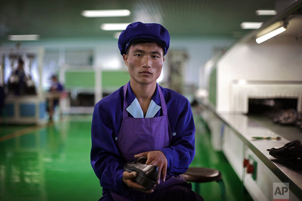 "In this June 22, 2016, photo, Kang Jong Jin, a 28-year old former soldier who attaches soles onto shoes at a shoe factory in Wonsan, North Korea, poses for a portrait at his work station. Kang, who has been working longer hours during this 200-day ""speed campaign"" in line with North Korean leader Kim Jong Un's vows to raise the nation's standard of living and energize his five-year plan to develop economy, says that he wants to contribute to Kim's plan by taking courses to improve his scientific and technological skills. (AP Photo/Wong Maye-E)"