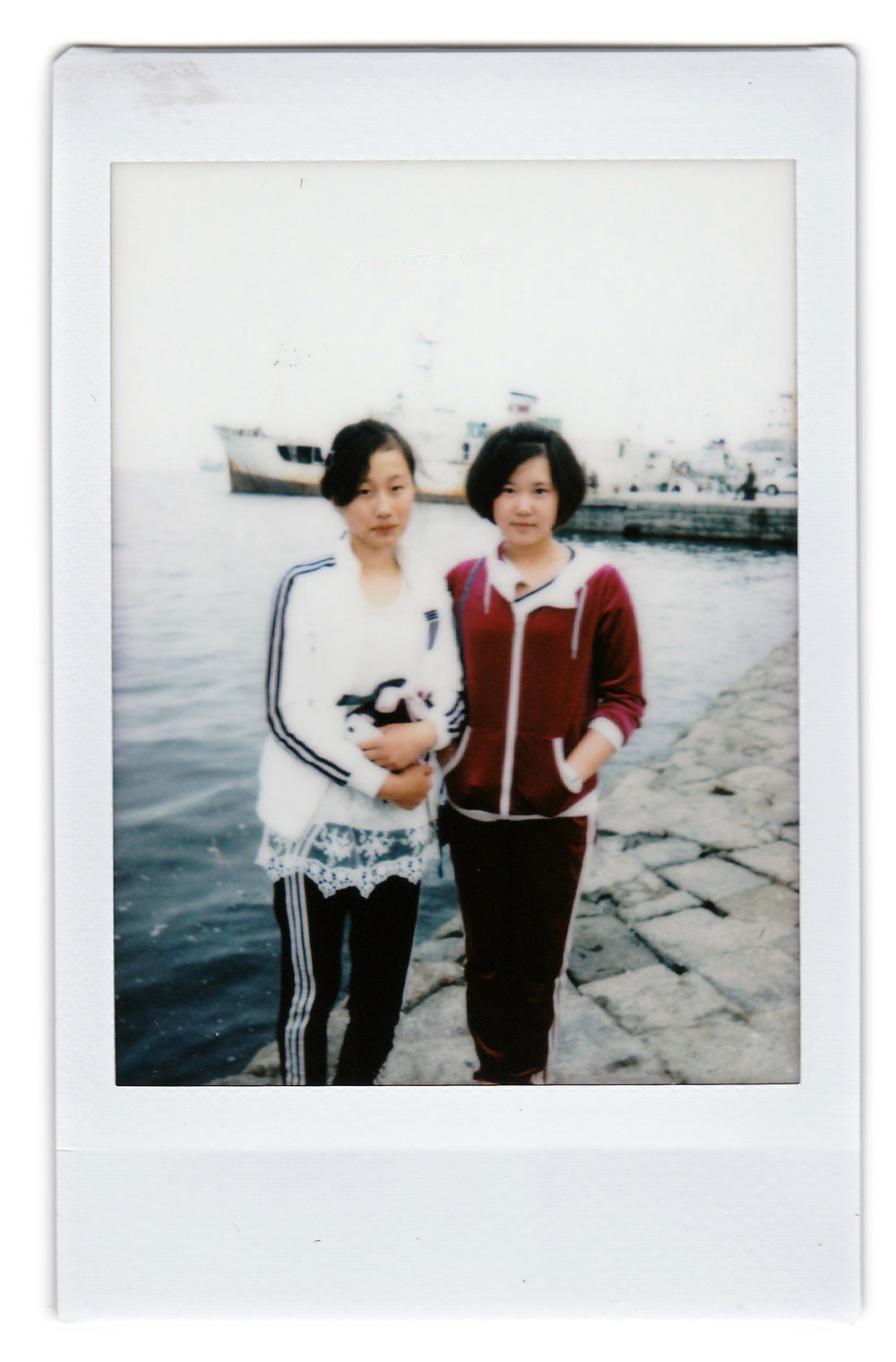 "In this June 21, 2016, photo made with an instant camera, Ri Nam Hae, left, and Kil Myong Kyong, both 16-years old, pose for a portrait at a pier in Wonsan, North Korea. When asked what's important to them, North Koreans might talk about working hard, or doing well at sports, or having a big family, but leader Kim Jong Un is never far from the conversation. Ri wants to be a journalist and her motto is to ""spread the country's propaganda to the world. "" Kil's motto: ""I want to uphold Marshal Kim Jong Un and North Korea with my rifle."" (AP Photo/Wong Maye-E)"