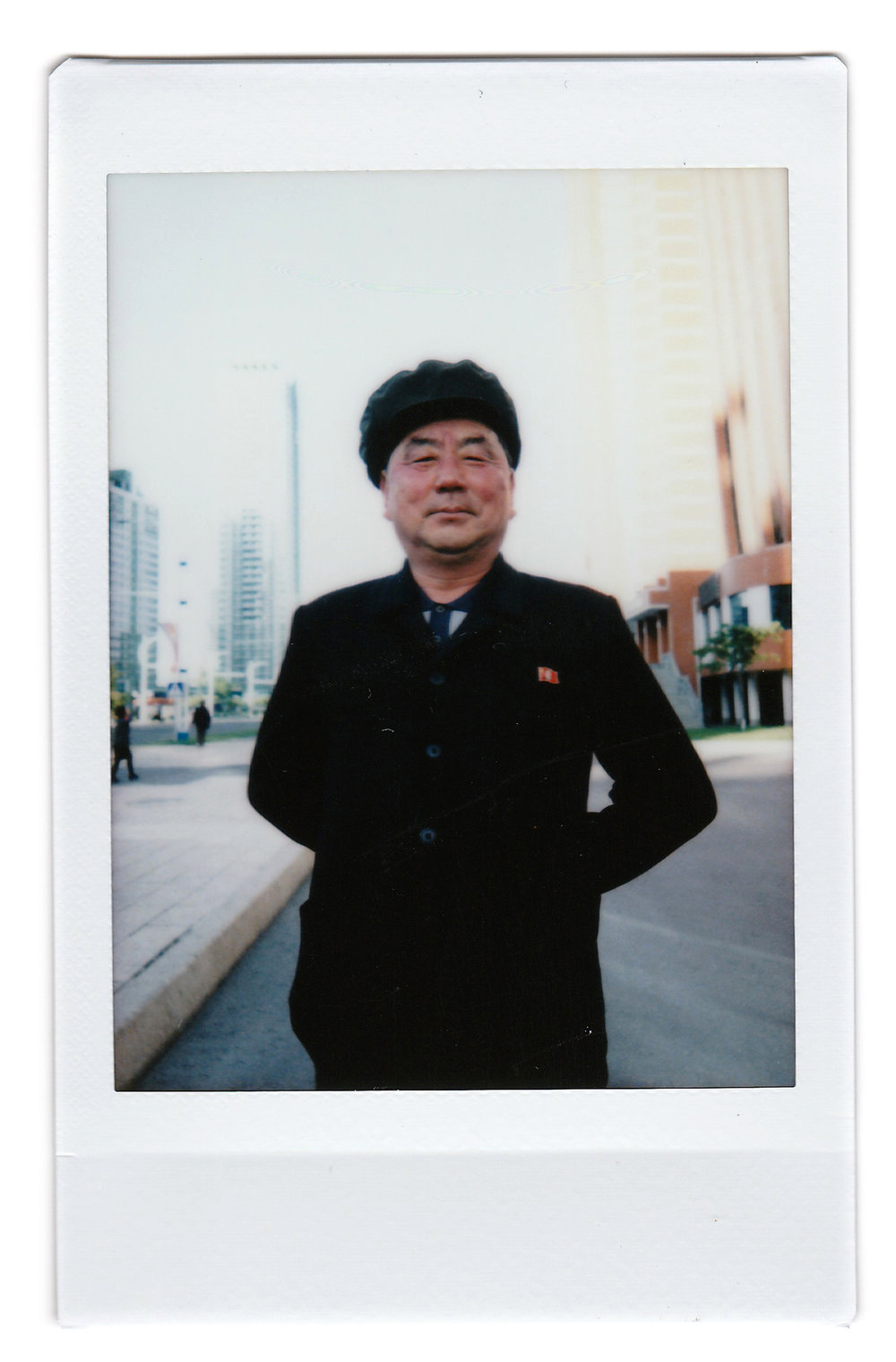 "In this May 7, 2016, photo made with an instant camera, Pak Su Won, 66, a retired local physician, poses for a portrait along Mirae Scientists Street in Pyongyang, North Korea. When asked what's important to them, North Koreans might talk about working hard, or doing well at sports, or having a big family, but leader Kim Jong Un is never far from the conversation. His motto: ""To devote myself to leader Kim Jong Un for the rest of my life. For him, and for the fatherland."" (AP Photo/Wong Maye-E)"